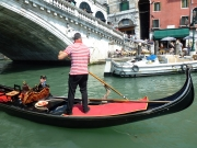 Gondolier going under bridge